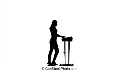 Silhouette. Piano. Girl playing fast music and claps. Studio...