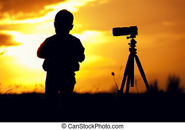 Silhouette picture of boy standing with camera