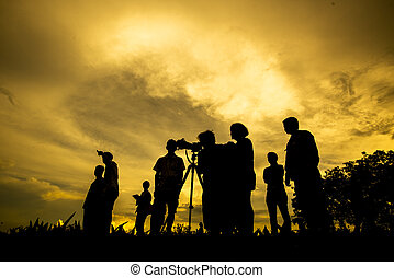 silhouette picture of many people with sunset