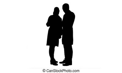 Silhouette Pretty female nurse and handsome doctor with stethoscope using digital tablet.