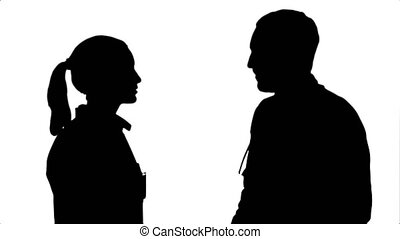 Silhouette Profile view of happy mature male and female doctors smiling while shaking hands.