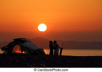 Silhouette romantic couple camping with tents on the beach