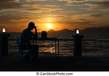 Silhouette sad man drinking beer at the beach with red sky sunset