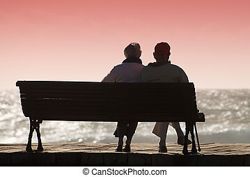 Silhouette seniors couple waiting for colourfull sunset on the bench