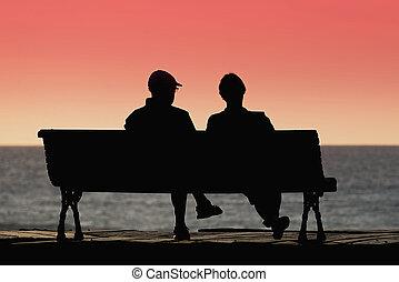 Silhouette seniors couple waiting for colourfull sunset