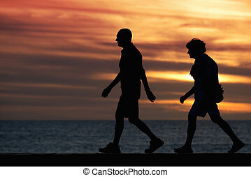 Silhouette seniors walking brisk walk