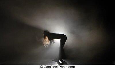 Silhouette sexy girl dancing in a smoky studio twerk dance