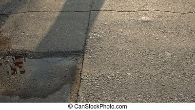 Silhouette unrecognizable persone walking in the street with sun casting shadow