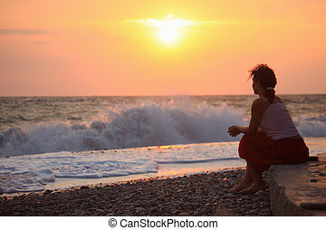 Silhouette sitting young woman on sunset wavy beach