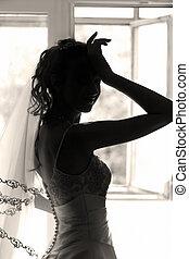 Silhouette - The beautiful bride prepares for wedding....