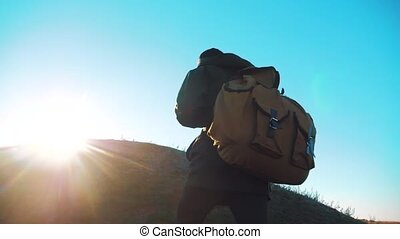 Silhouette teen boy hikerof backpacker. steadicam motion video sunlight sunset person side view walking toward successful. lonely teenager boy with sunset background. Travel and success concept the adventure lifestyle