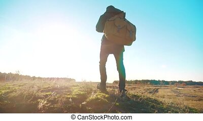 Silhouette teen boy hikerof backpacker. steadicam motion video sunlight sunset person side view walking toward successful. lonely teenager boy with sunset background. Travel and lifestyle success concept the adventure