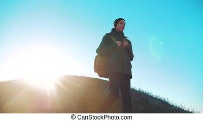 Silhouette teen boy hikerof backpacker. steadicam motion video sunlight sunset person side view walking toward successful. lonely teenager boy with sunset lifestyle background. Travel and success concept the adventure