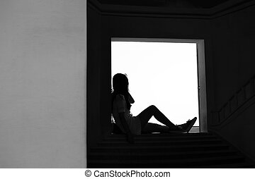 silhouette teen girl sitting on door step thinking in black and white