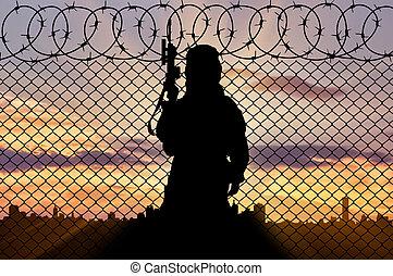 silhouette, terrorist, bei, der, umrandungen, zaun, in, der, hintergrund, von, stadt, an, sonnenuntergang