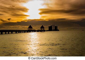 Silhouette The long bridge over the sea with a beautiful sunrise.