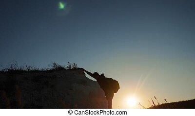 silhouette tourist climber climbs a mountain. walking...