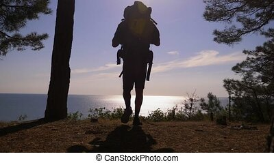 silhouette tourist man with a large backpack travels to the...