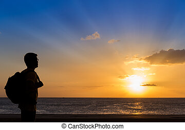 Silhouette traveler with backpack standing near the beach at sun