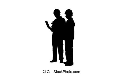 Silhouette Two experienced industrial technicians work on...