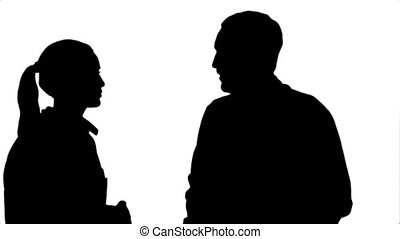 Silhouette Two medical professionals discuss with a patient.