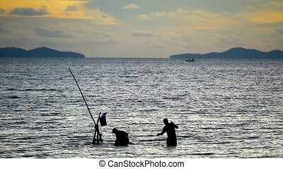 Silhouette two men at sea collecting nets to separate the ...