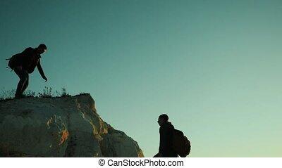 silhouette two men teamwork tourists climber climbs a...