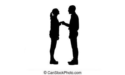 Silhouette Two young people in casual shake hands, look at camera and thumb up.