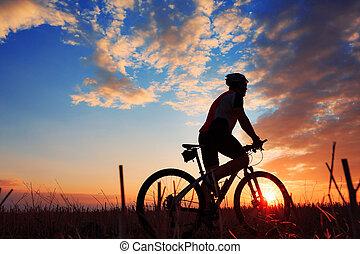 silhouette, van, een, fietser, en, fiets, op, ondergaande zon , achtergrond.