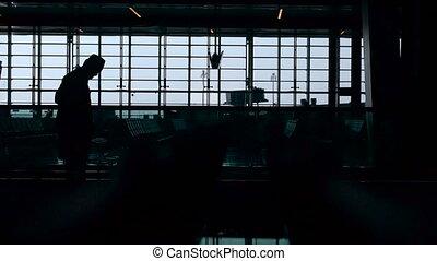 silhouette, van, een, man, in, een, hoedje, wie, ritten, op, de, roltrap, op, de, luchthaven., een, groot, venster, op, de, achtergrond., moderne technologie, in, alledaags, life.