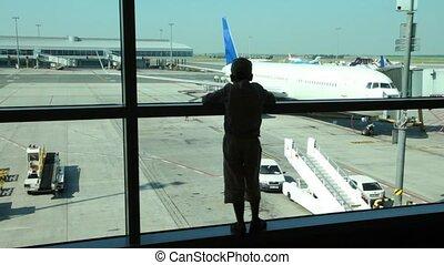 silhouette, van, jongen, blik, door het venster, op, vliegtuigen op de luchthaven