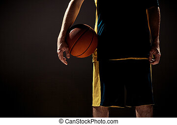 Silhouette view of a basketball player holding basket ball on black background