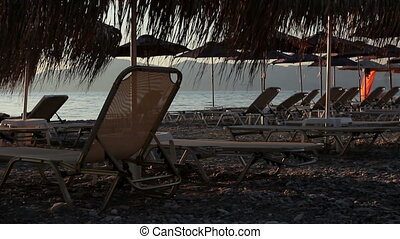 Silhouette view of thatched umbrellas with loungers next to the coastline