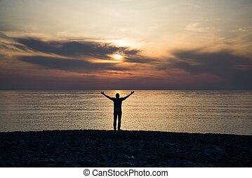 silhouette, von, a, mann, mit, angehobene arme, in, der, meerwasser, an, sonnenuntergang