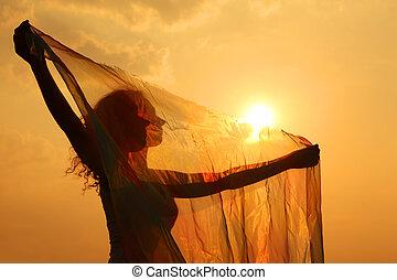silhouette, von, frau, mit, durchsichtig, tuch, in, seine, hände, an, sonnenuntergang