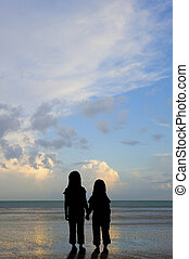 Silhouette vulnerable kids on sunset beach - Silhouette of...