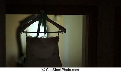 silhouette wedding dress hanging on a hanger