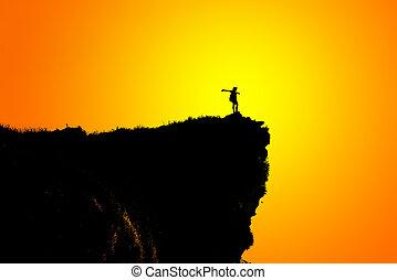 Silhouette woman on peak mountain