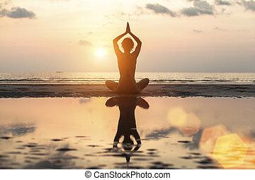 Silhouette woman yoga on the beach