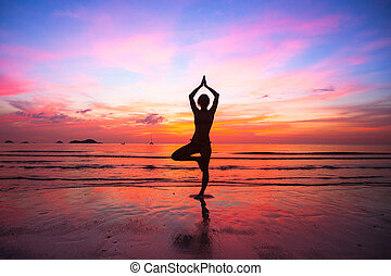Silhouette woman yoga practice at the seaside at sunset.