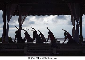 silhouette women practicing yoga on beach