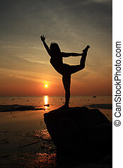 Silhouette yoga girl by the beach at sunrise doing Lord of the Dance Pose