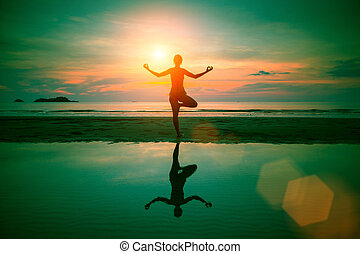 Silhouette yoga woman on sea coast at surreal sunset (abstract photo about healthy lifestyle)