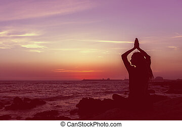 Silhouette yoga woman on the beach at sunset. Meditation.
