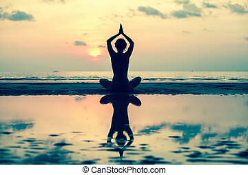 Silhouette yoga woman on the sea beach at sunset.