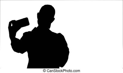 Silhouette Young pretty female doctor makes selfie on smart phone.