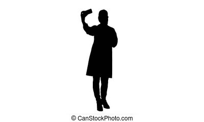 Silhouette Young pretty female doctor makes selfie on smart phone smiling.