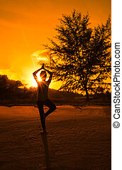 Silhouette young woman play yoga on the beach with sunlight.