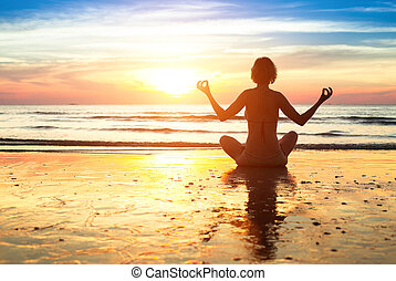 Silhouette young woman practicing yoga on the beach at sunset.