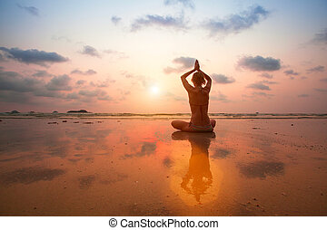 Silhouette young woman practicing yoga on the sea beach at sunset.